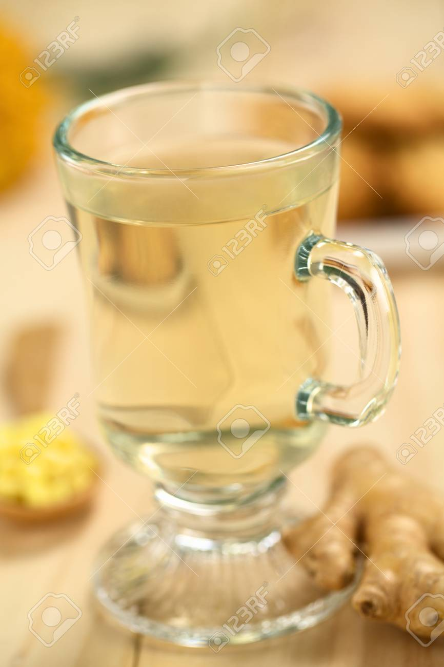 Freshly prepared hot ginger tea made of fresh ginger root served in glass (Selective Focus, Focus on the front of the rim and the handle of the glass) Stock Photo - 23791017