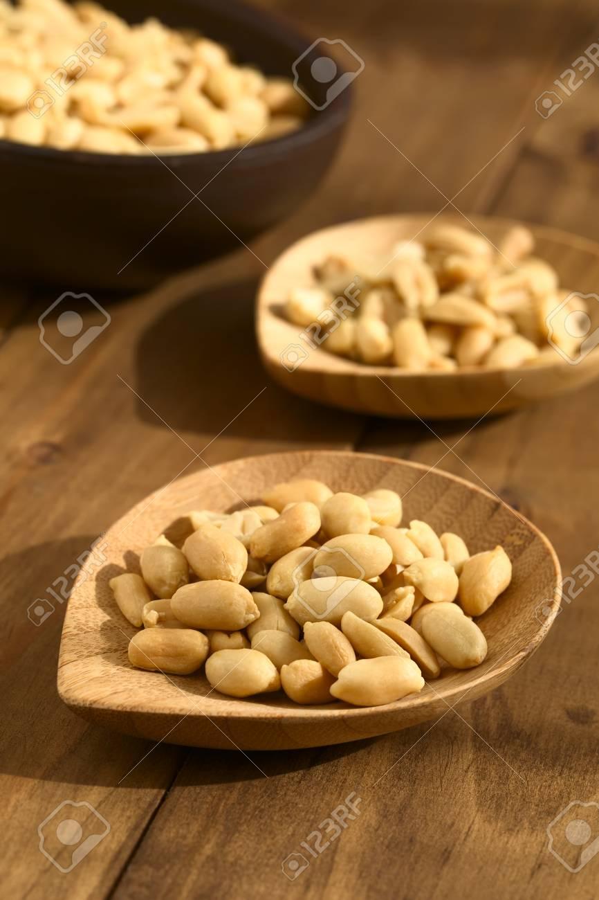 geröstete geschälte ungesalzene erdnüsse auf kleiner bambusplatte