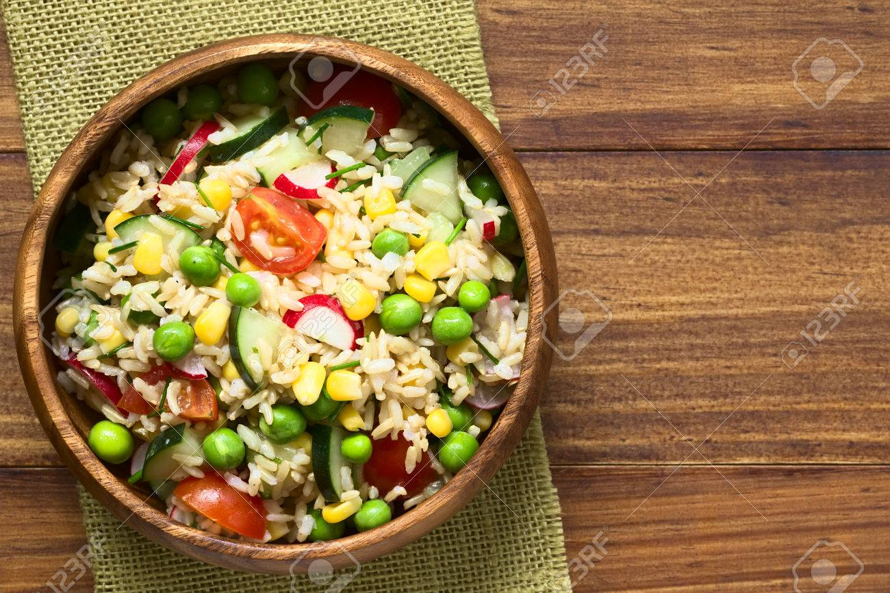 Brown rice salad with cherry tomato, corn, cucumber, radish, pea and chives served in bowl, photographed overhead on dark wood with natural light (Selective Focus, Focus on the top of the salad) - 55971835