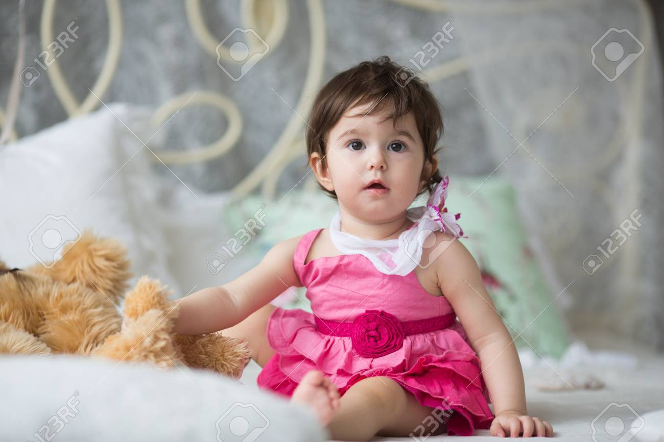 cute girl, princess, a child in a pink dress on the white bed stock