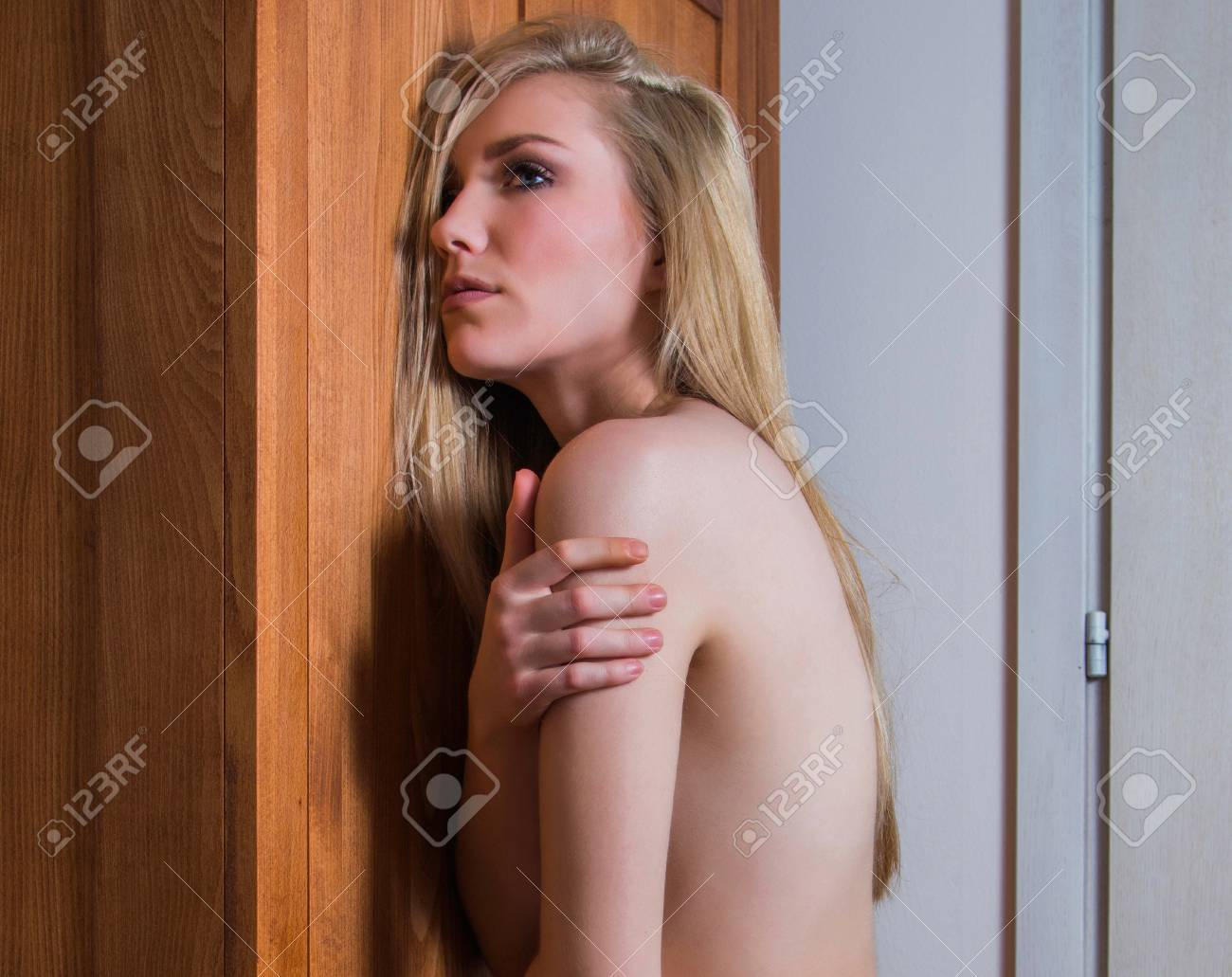 young nude sexy lady leaning on old wooden retro vintage locker
