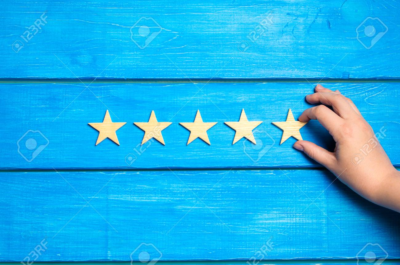 The hand puts the fifth star. The critic determines the rating of the restaurant, hotel, institution. - 103699972