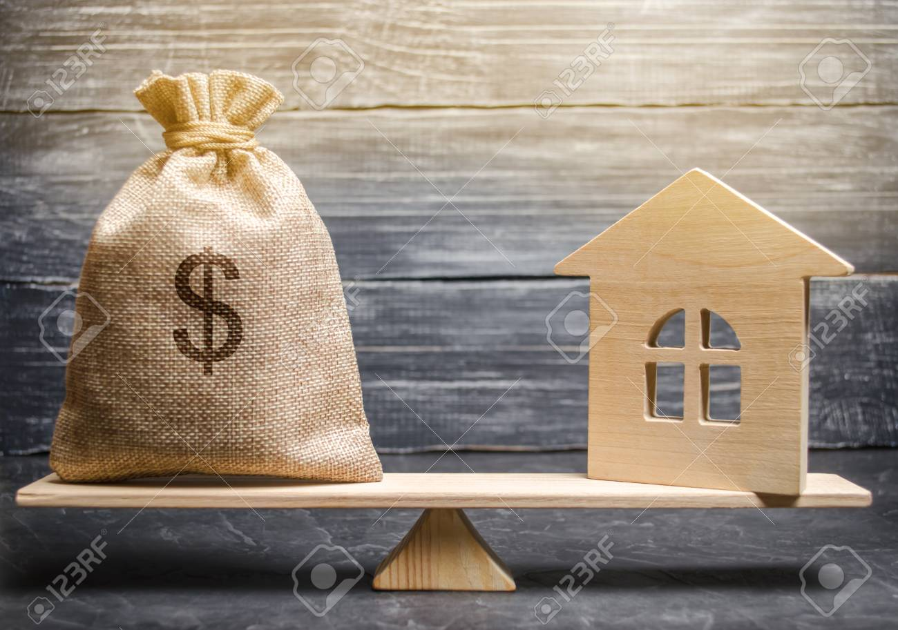 A money bag and a wooden house on the scales. The concept of real estate purchase. Sale of property. Payment of the mortgage. Redemption of taxes. Tax refund. Legacy / Inheritance tax concept - 117670292