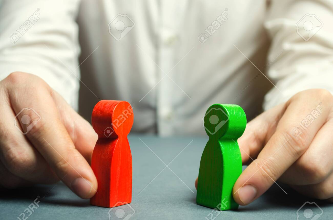 A man holds in his hands the red and green figures of people facing each other. Conflict resolution, conflict of interest. The search for a compromise, mediation in negotiations. Weave intrigue. - 118036419