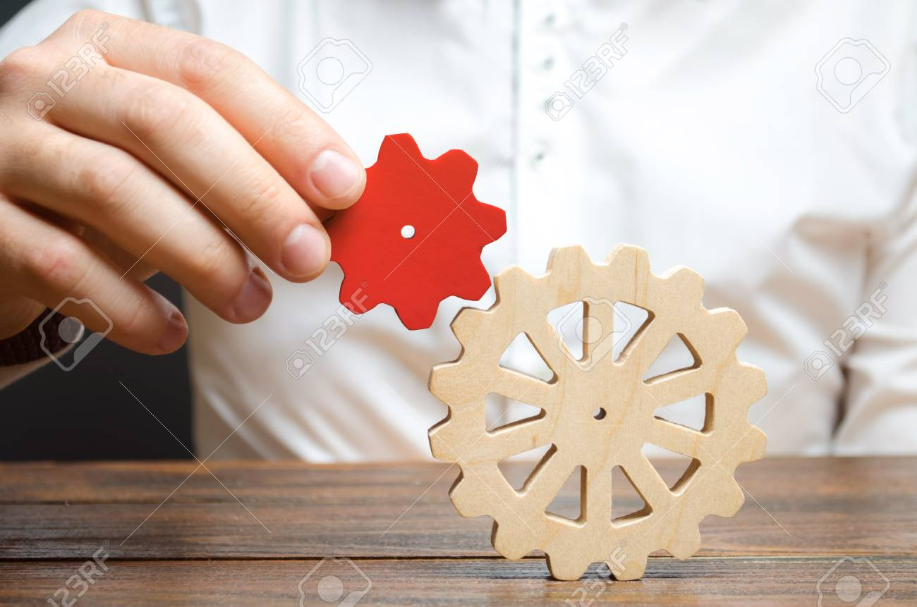 Businessman connects a small red gear to a large gear wheel. Symbolism of establishing business processes and communication. Increase efficiency and productivity. The best business formula for success - 120127721