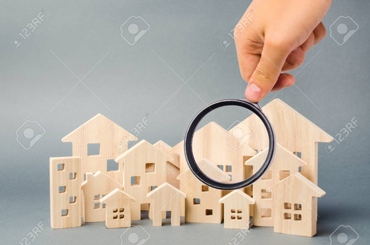 Wooden houses and magnifying glass. Property valuation. Home appraisal. Choice of location for the construction. House searching concept. Search for housing and apartments. Real estate - 124956041