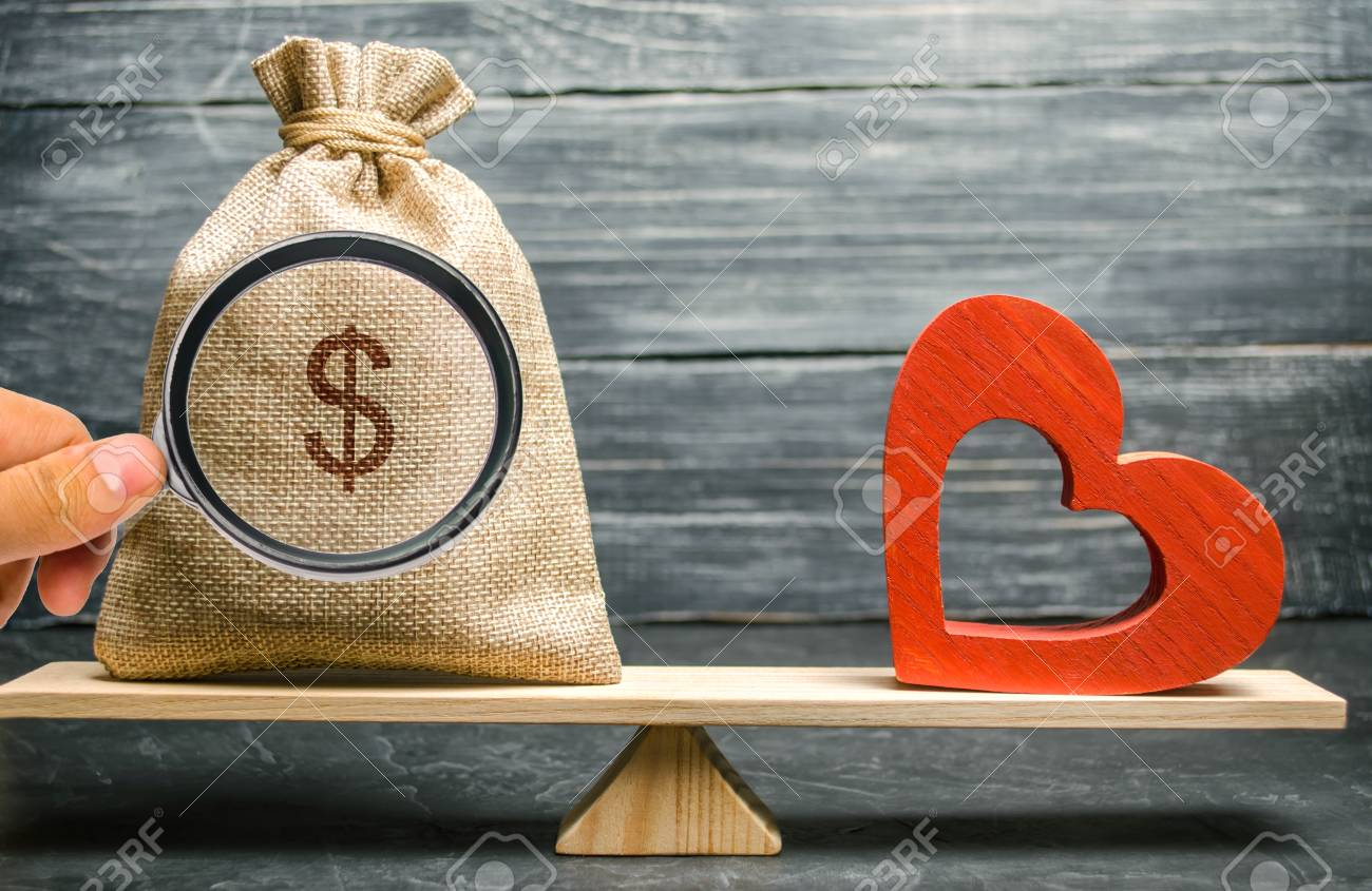 Bag with money and red wooden heart on the scales. Money versus love concept. Passion versus profit. Family or career choice. Family psychology. Mind vs. Passion - 124957907
