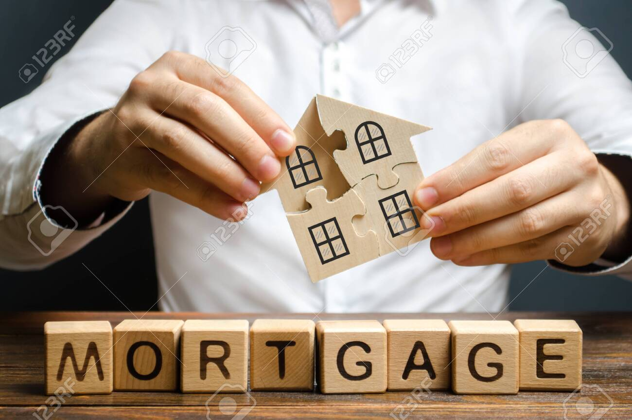 A man collects a house from the puzzles over the inscription Mortgage. Construction of your own residential building. Buying a home on credit loan, improvement of living conditions - 130552482