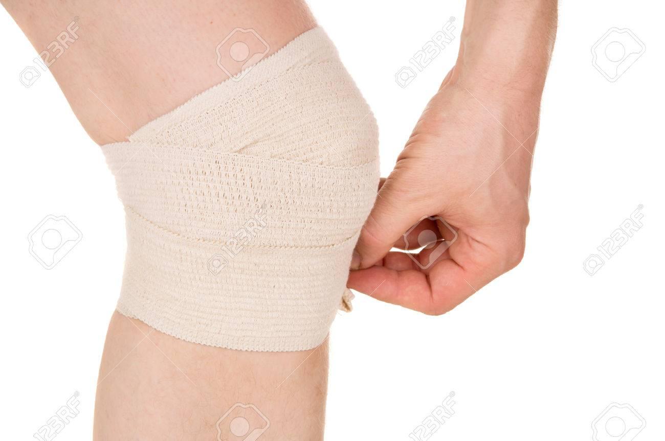 Bandaging The Knee With An Elastic Bandage Isolated On White