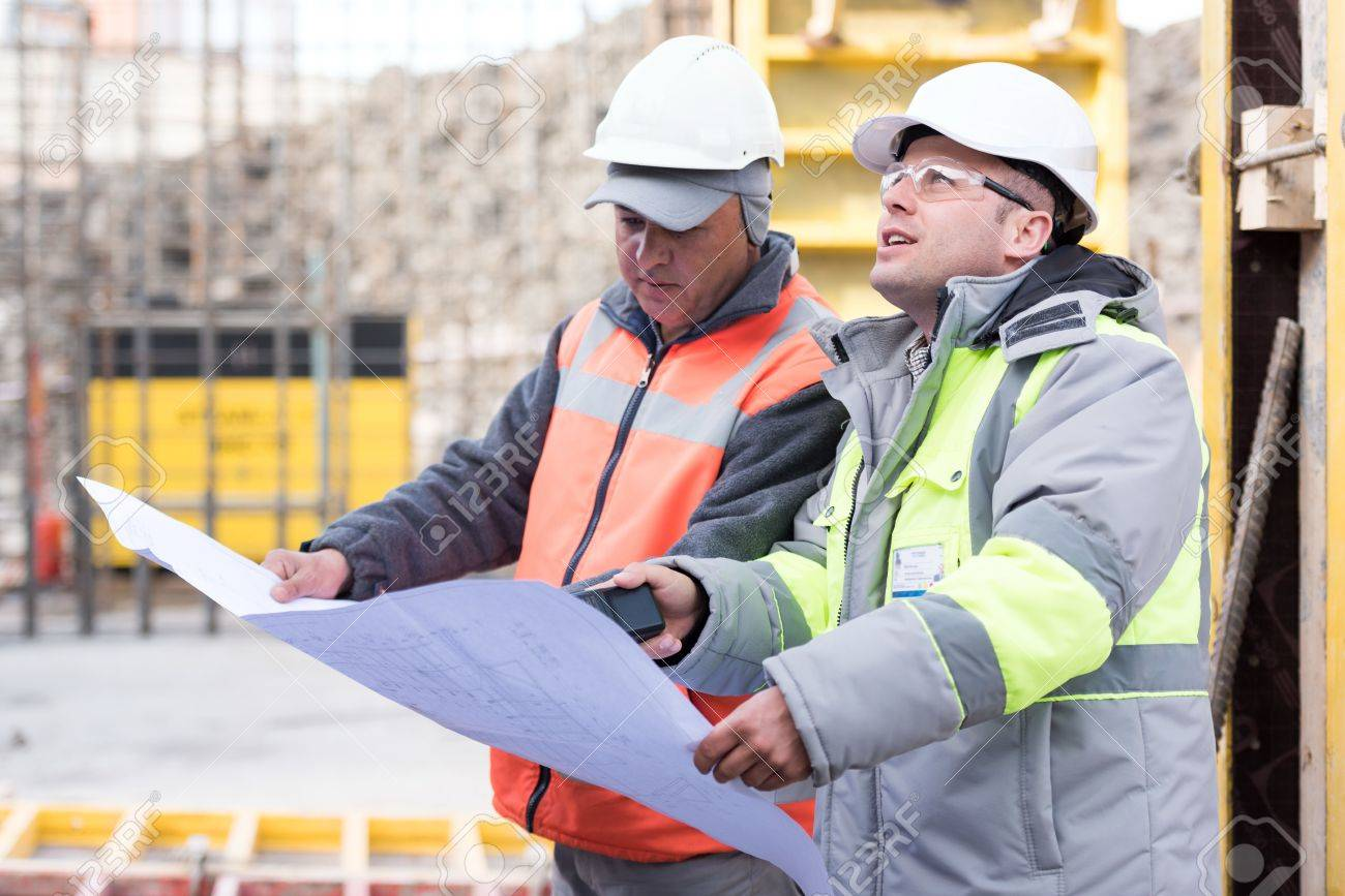 Civil Engineer And Foreman At Construction Site Are Inspecting Ongoing  Works According To Design Drawings.  Civil Engineer