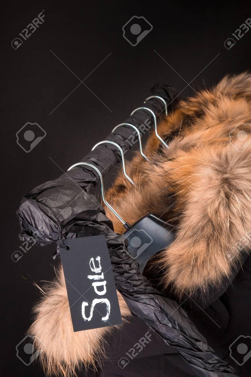 ef8c44f08b9f Viele schwarze Mäntel, Jacke mit Fell auf der Kapuze am Kleiderständer.  Schwarzer Hintergrund.