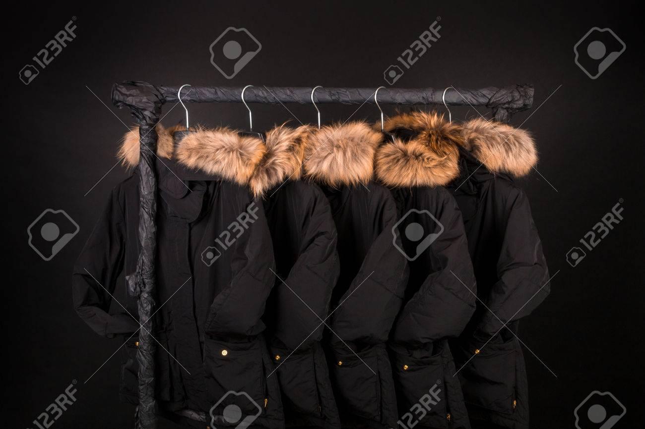 a5f0199f4d20 Viele schwarze Mäntel, Jacke mit Pelz auf der Kapuze, die am Kleiderständer  hängt.
