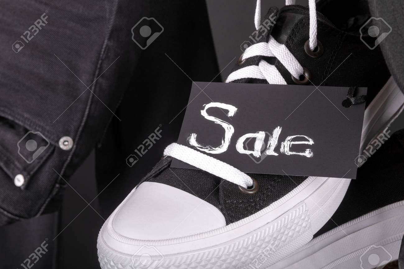2d89dbb67534 Sale sign. Hanging black and white sneakers near jeans on black background.  Friday sale
