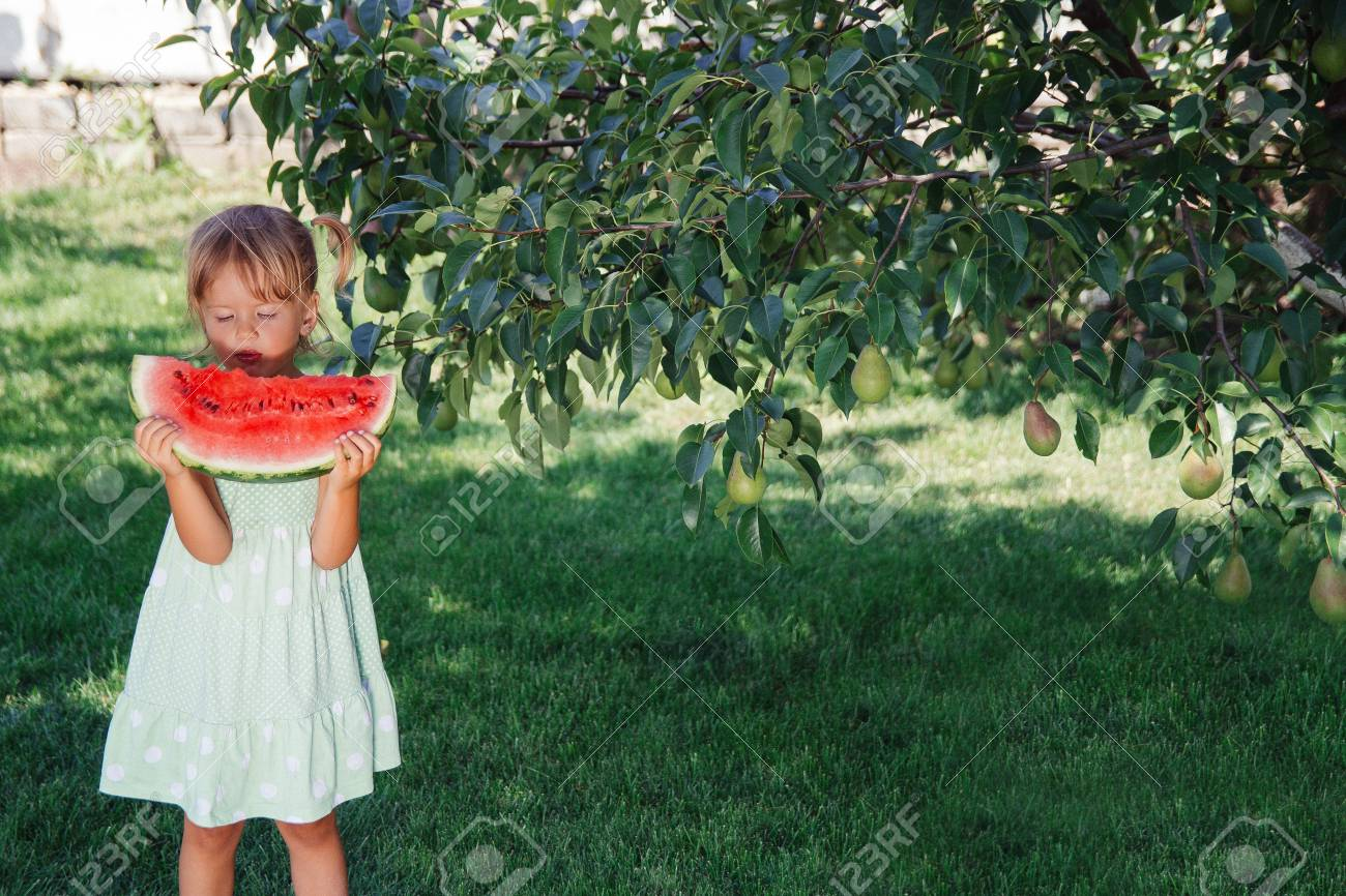 17be1151a967 Little girl in green dress, barefoot standing in the park with big slice  watermelon.