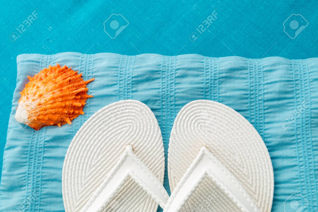 3c6b7f2d6 White flip flop near seashell on blue background. Top view Stock Photo -  76920335