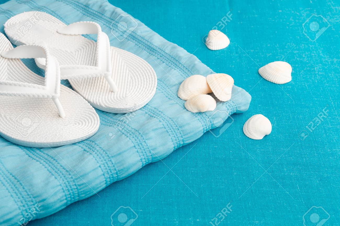 899a33631 Stock Photo - White flip flop near seashell on blue background. Summer.  Vacation