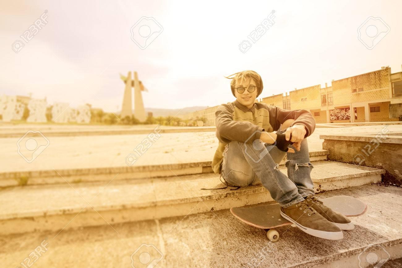 56f0b8d564920 Foto de archivo - Joven chico rasta aire libre sentado en su skate con un  filtro cálido aplicado