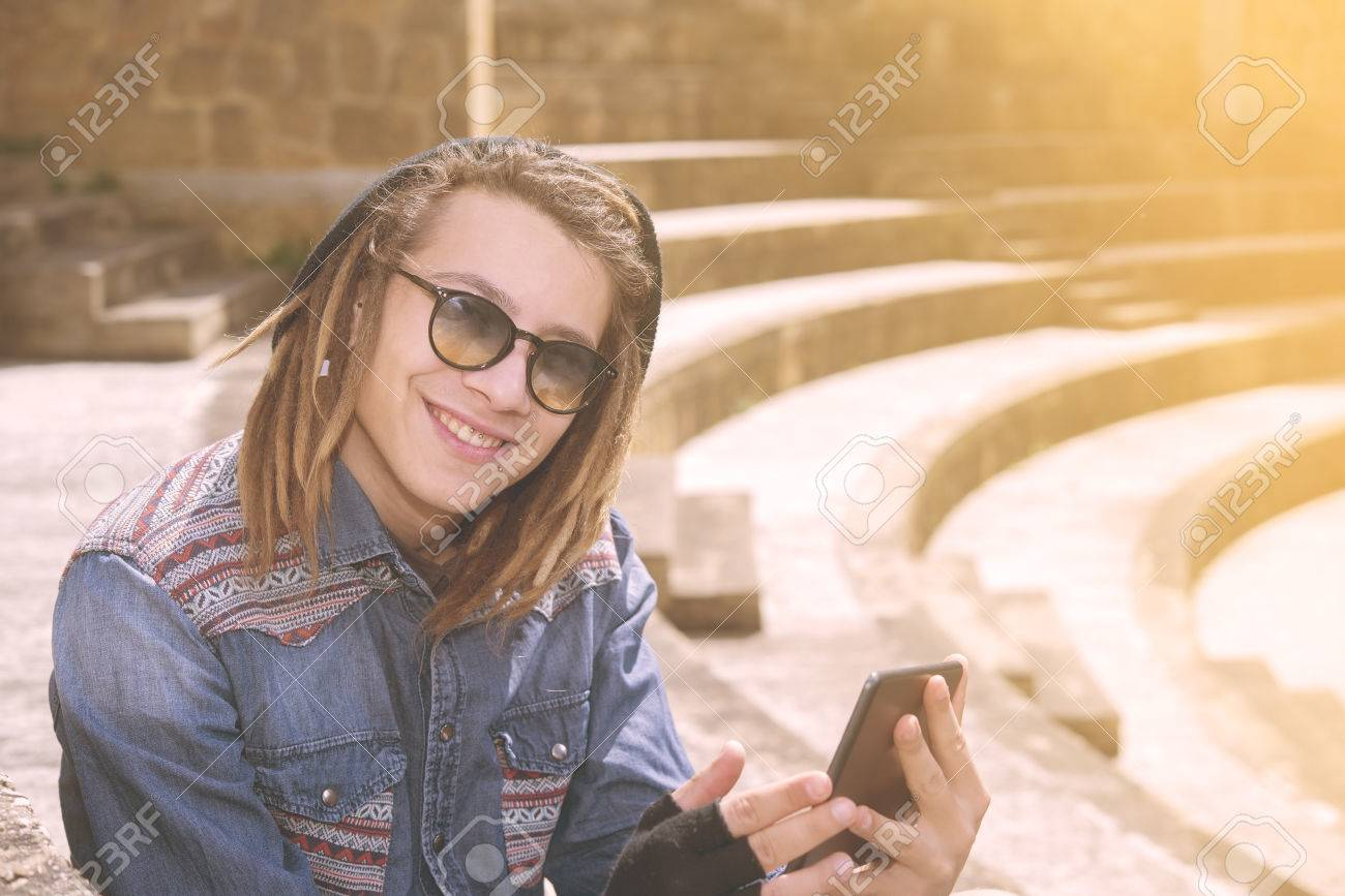 6ec0452b82f freelancer guy with dreadlocks sitting on staircase with digital tablet  typing message warm filter applied