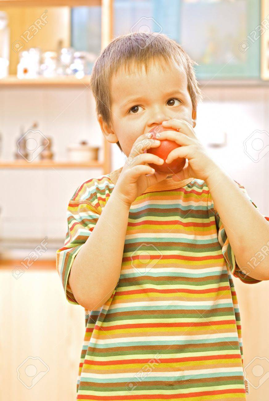 Happy boy eating a healthy, appetising apple Stock Photo - 2780380