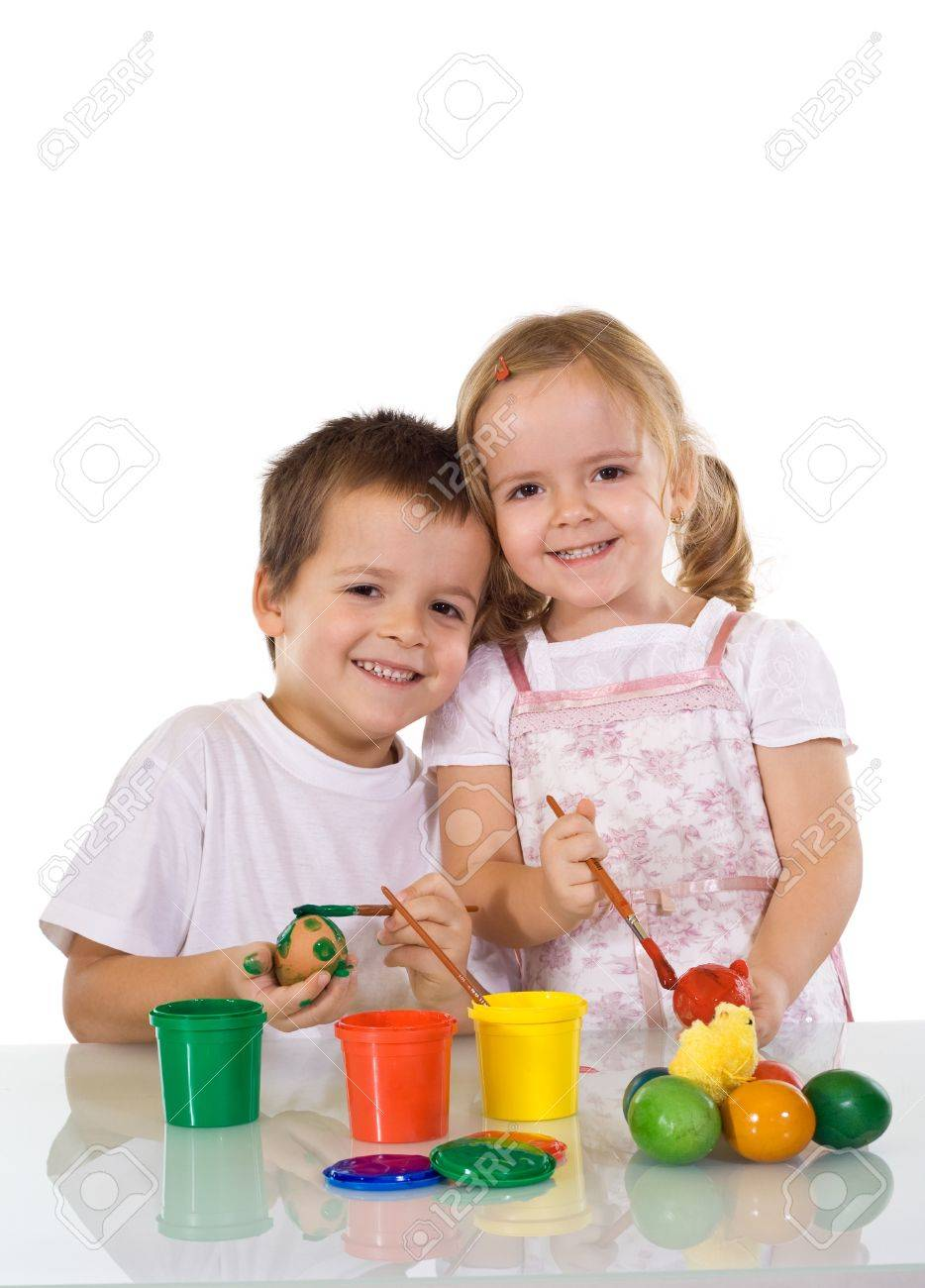 Happy kids painting the easter eggs together - isolated Stock Photo - 4143469
