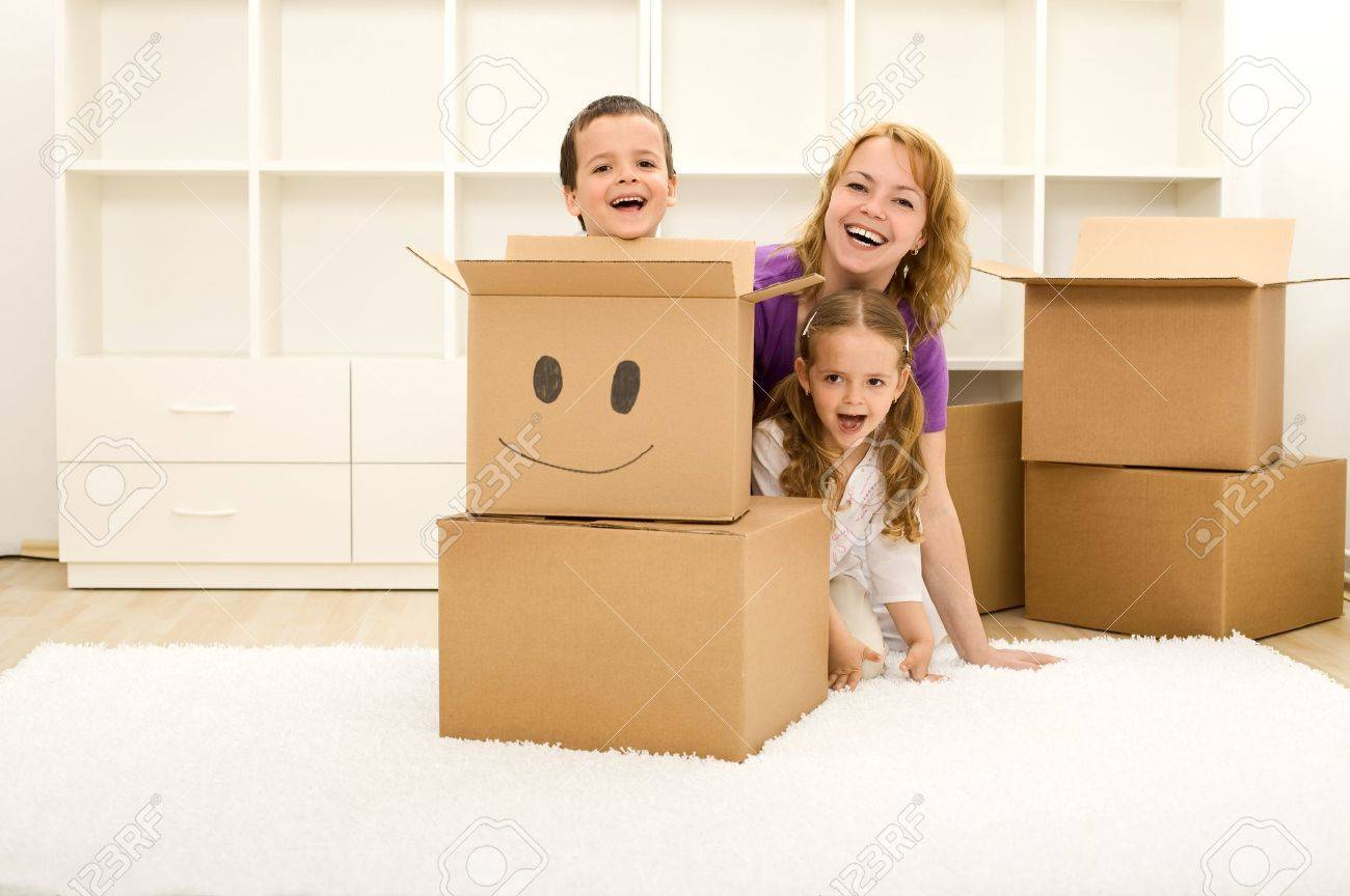 Happy kids and woman having fun in their new home playing among cardboard boxes Stock Photo - 7857255