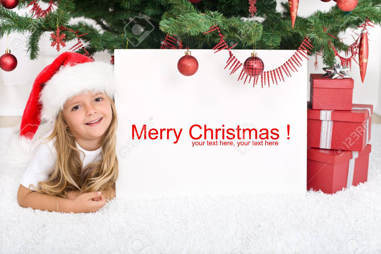 Little girl laying under the christmas tree with banner for text Stock Photo - 8114463