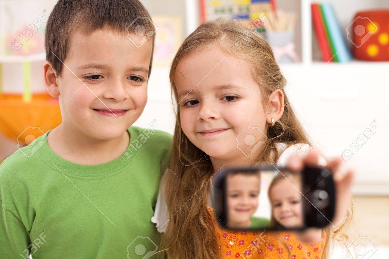 Kids taking a photo of themselves using a modern mobile phone Stock Photo - 9219596