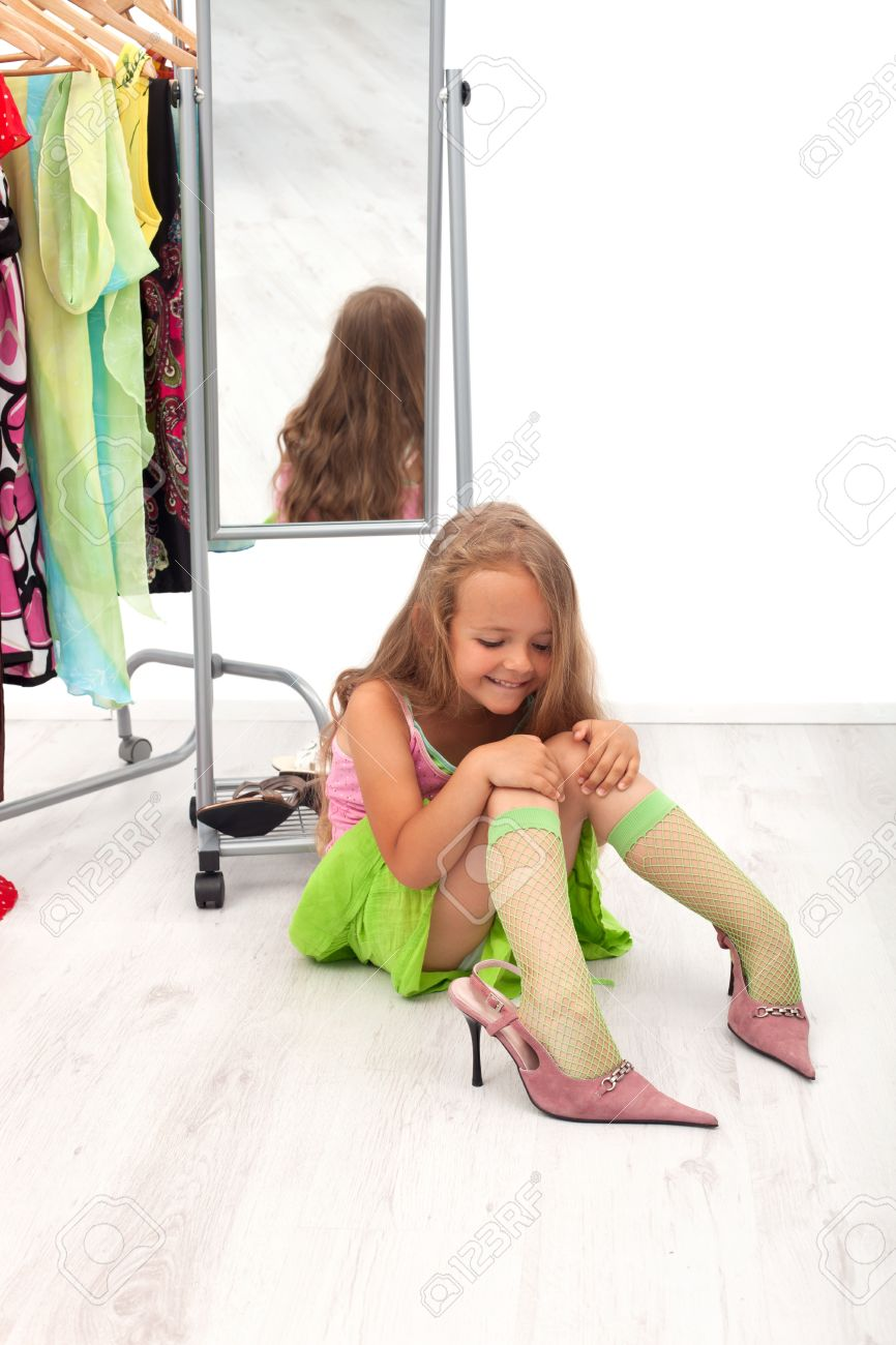 139bf4ed756 Little girl sitting on the floor trying on high heel shoes