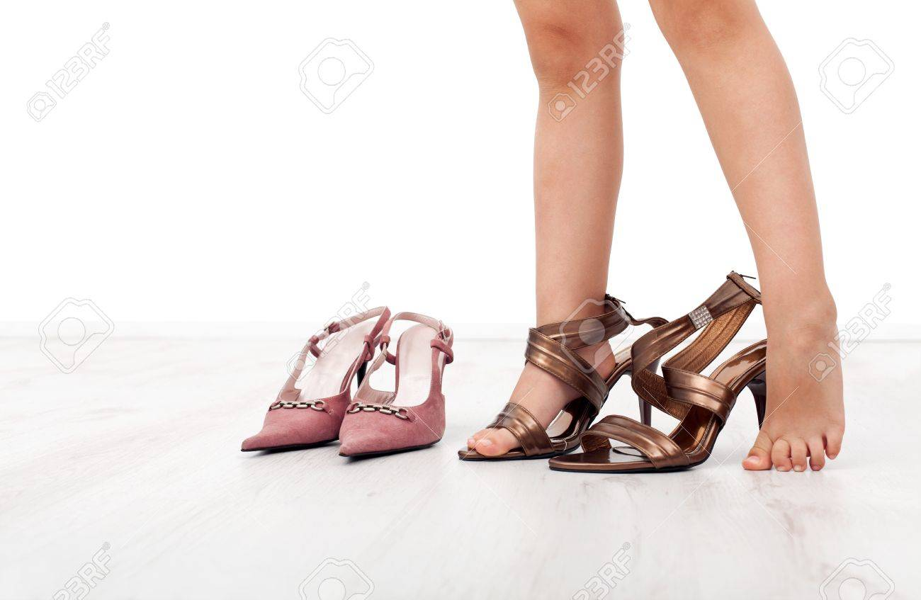 girlfeet Little girl feet trying large shoes with high heels Stock Photo - 9957147