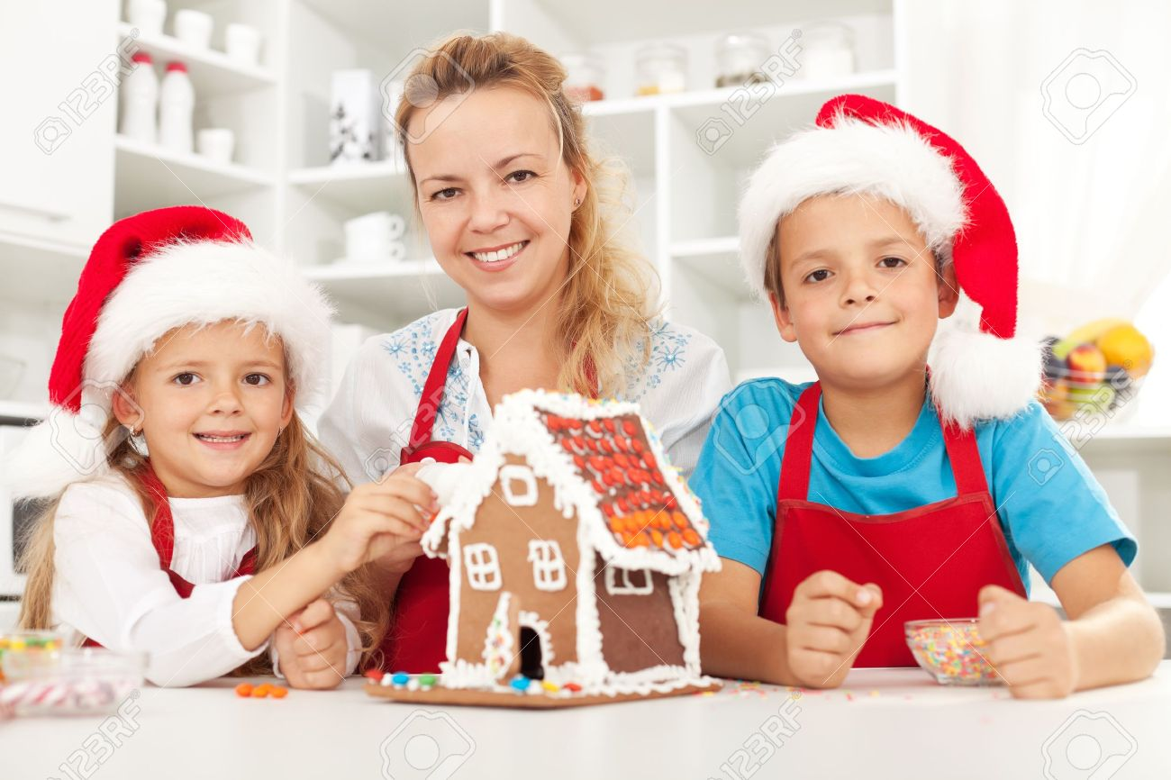 Happy christmas family in the kitchen decorating a gingerbread house Stock Photo - 10744874