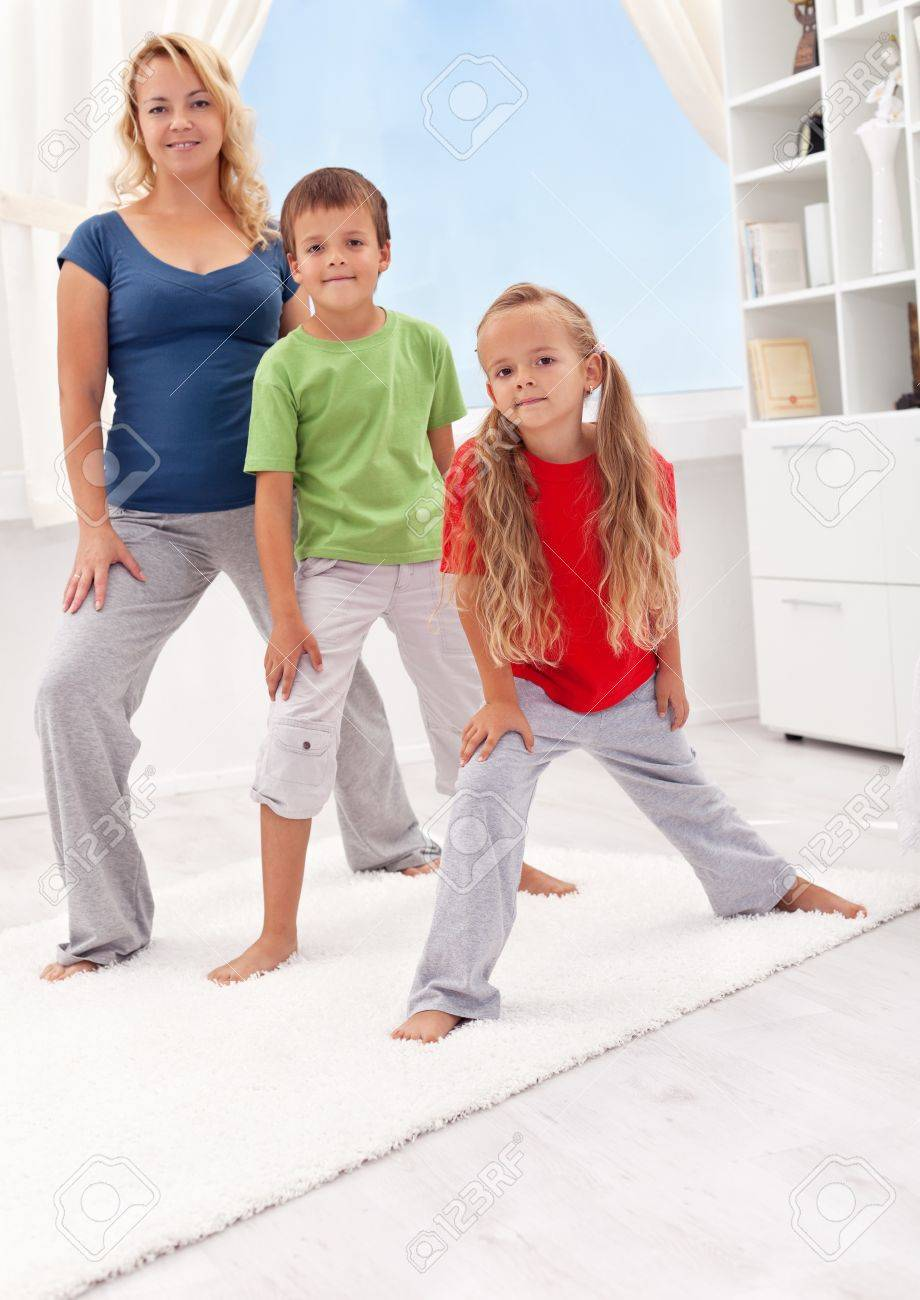 People exercising at home - woman with her kids stretching Stock Photo - 10986834