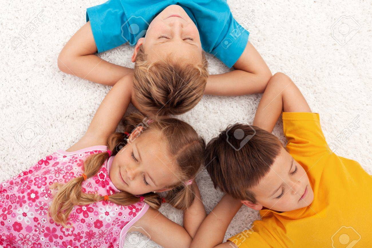 Kids taking a break relaxing on the floor with eyes closed Stock Photo - 11411299
