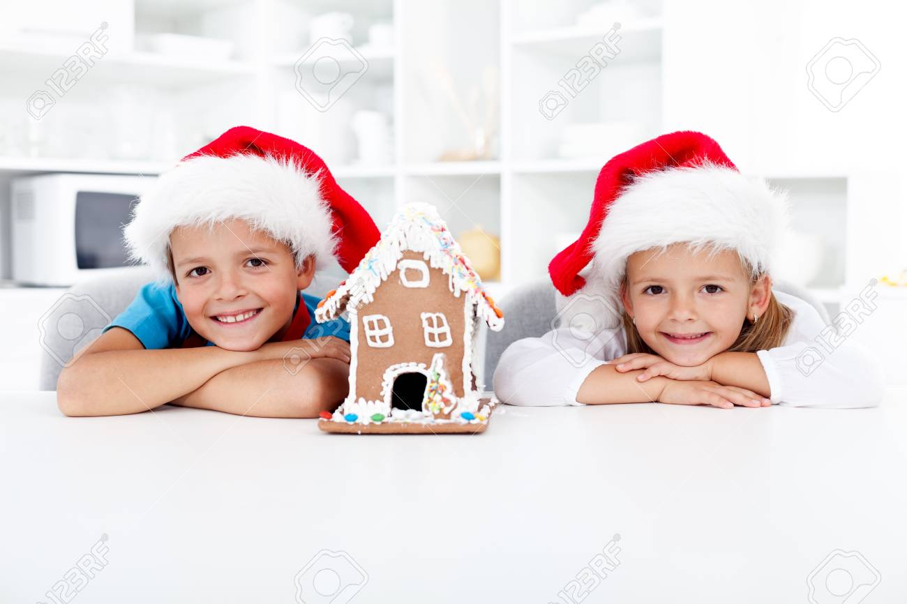 Happy kids with their gingerbread house in the kitchen at christmas time Stock Photo - 11411240