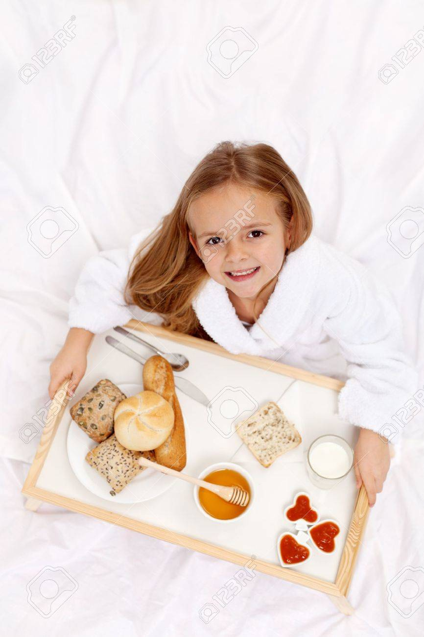 Happy little girl having a light breakfast in bed - top view Stock Photo - 11411304