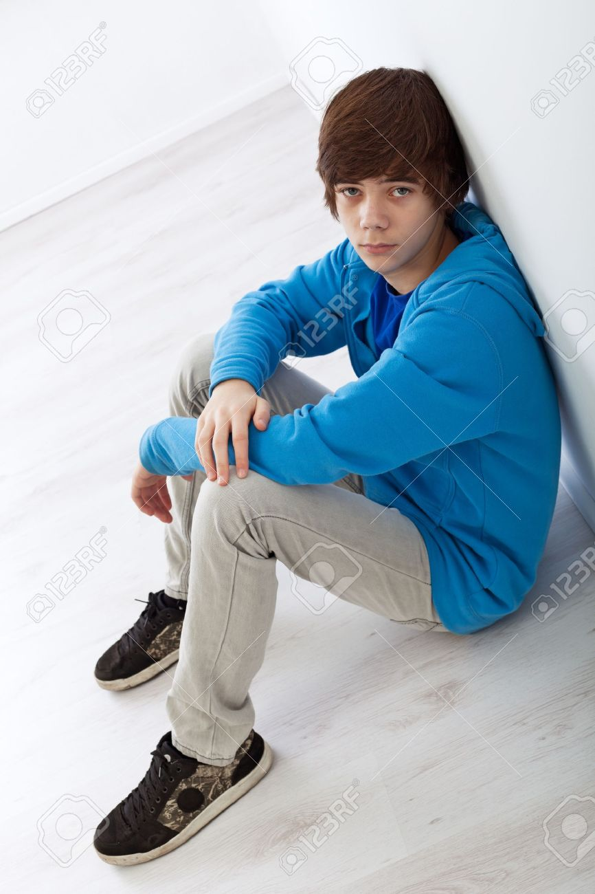 Sad teenager boy sitting on the floor leaning against the wall Stock Photo - 12078539
