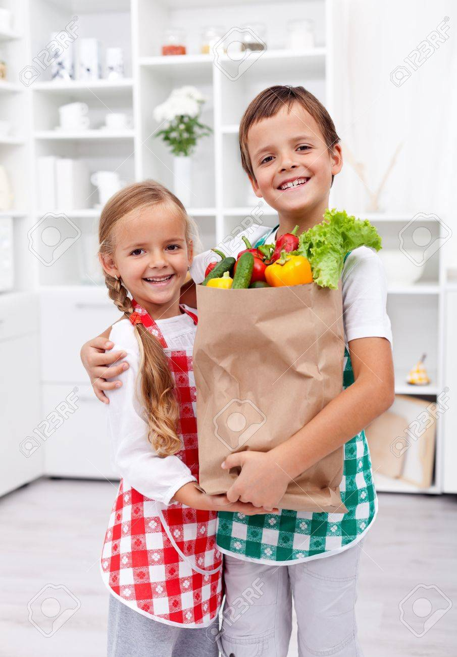 Happy healthy kids in the kitchen with the grocery bag full of vegetables Stock Photo - 12030711