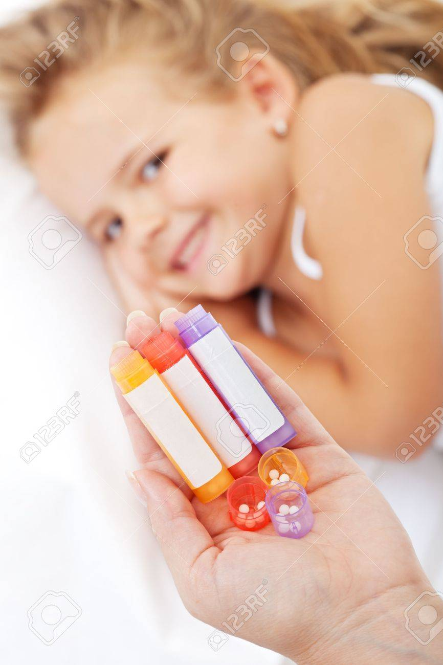 Homeopathic medication in woman hand - little smiling girl in background Stock Photo - 15380071