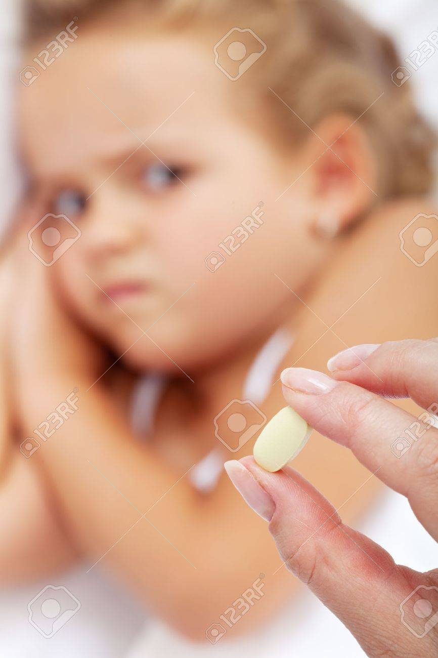 Little girl making faces to her medication - focus on the pill Stock Photo - 15720200