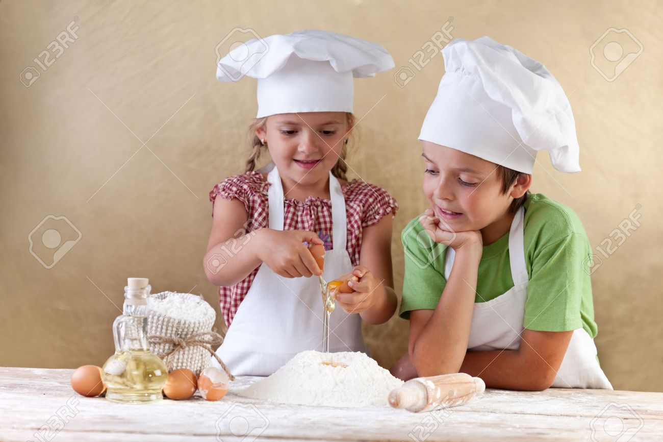 Kids with chef hats preparing tha cake dough - mixing ingredients - 15891808