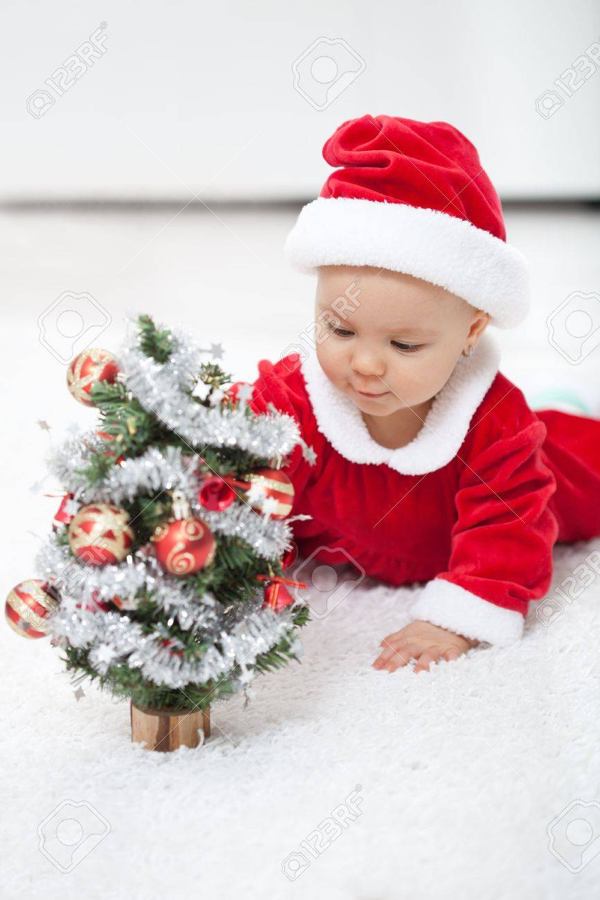 e8572f4c6 My first christmas - baby girl in santa outfit with small decorated..