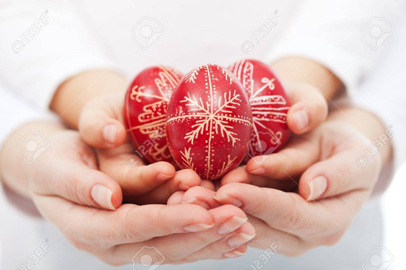 Woman and child hands holding traditional red easter eggs - 18267080