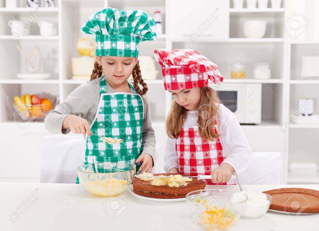 Little girls with chef hats preparing a cake in the kitchen Stock Photo - 18494350