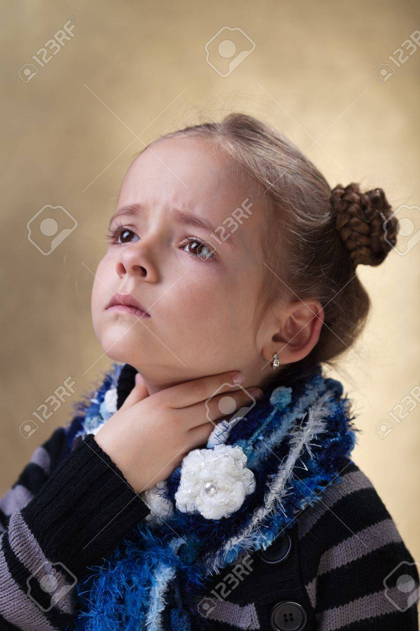 Little girl with sore throat in flu season touching her neck - 18494344