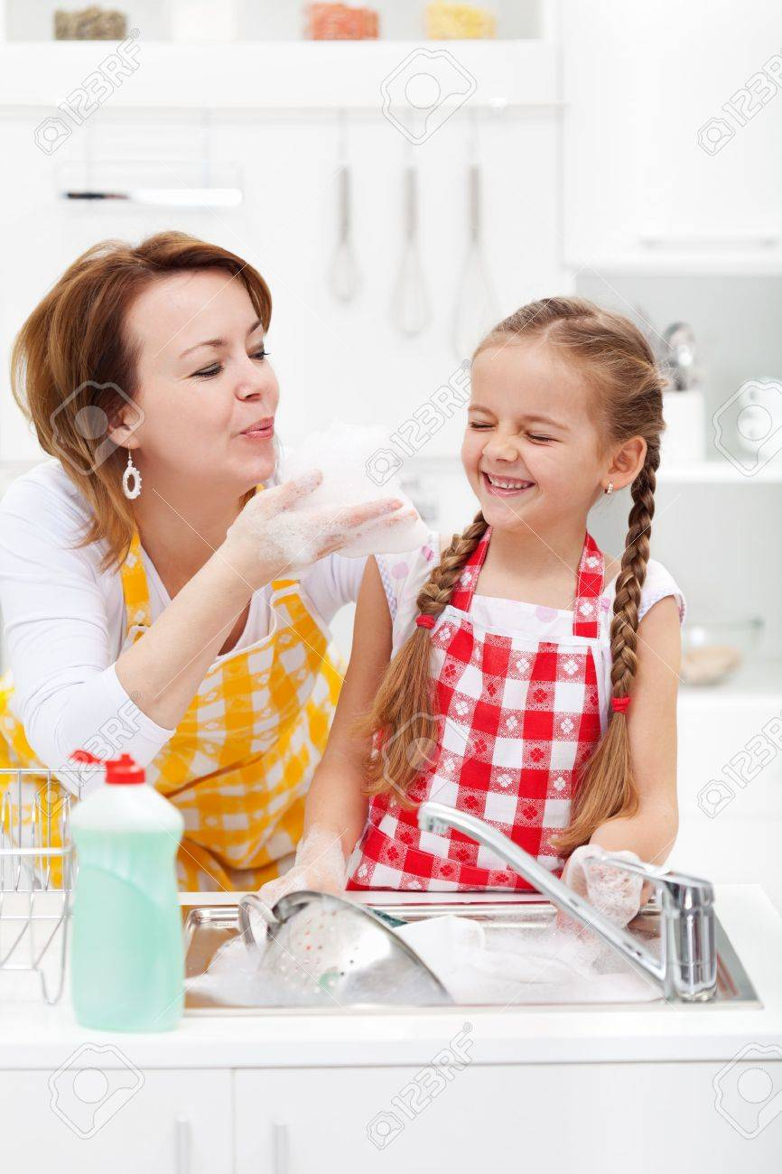 Woman and little girl having fun washing the dishes - playing with the foam - 19337287