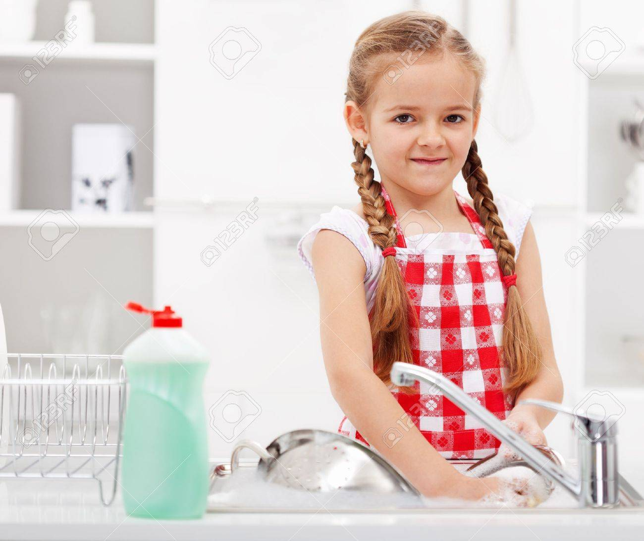 Little girl washing dishes in the kitchen - closeup - 20451482