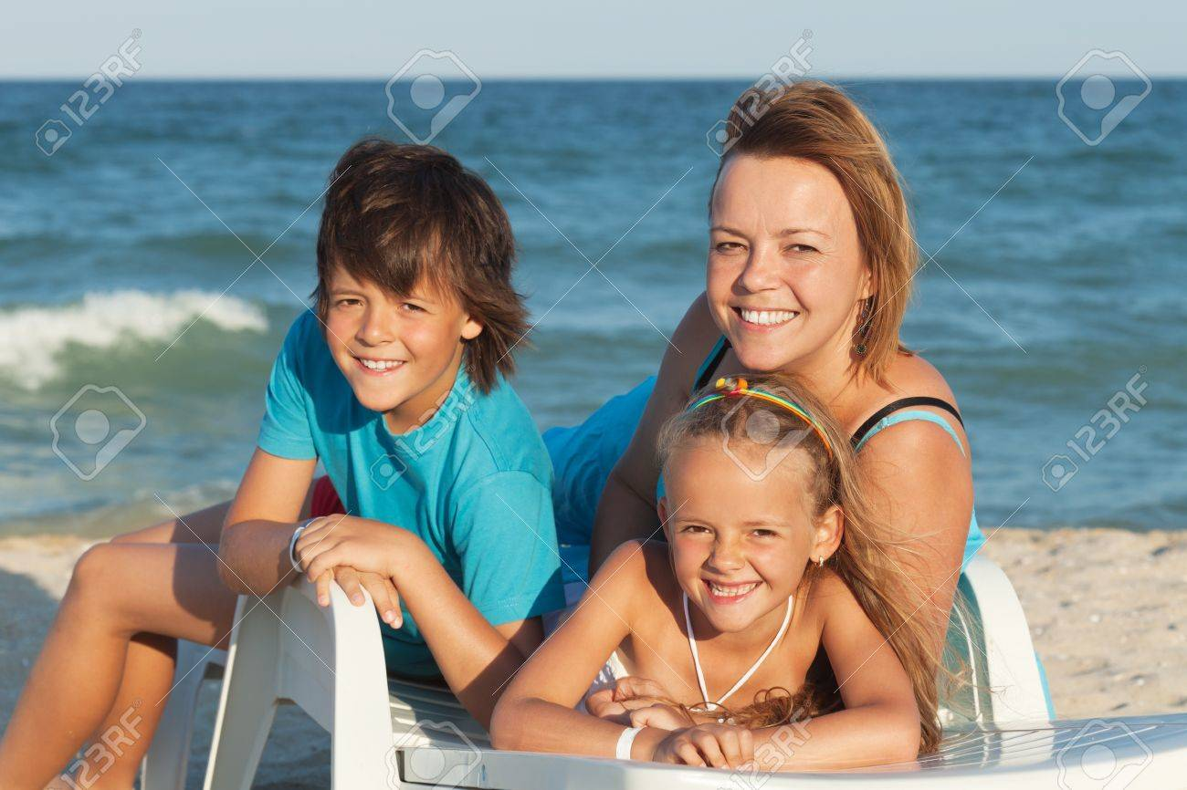 Happy woman and kids relaxing on a deck chair by the sea - summer beach portrait - 20905241