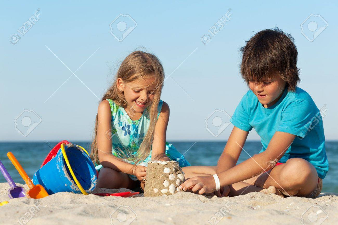 Kids playing on the beach building a sand castle decorating it with seashells - 21032070