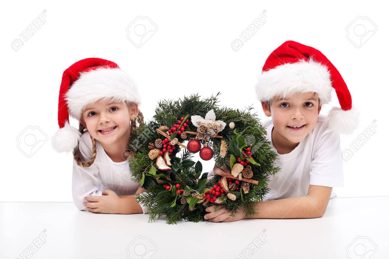Kids with traditional advent wreath wearing santa hats - 22426647