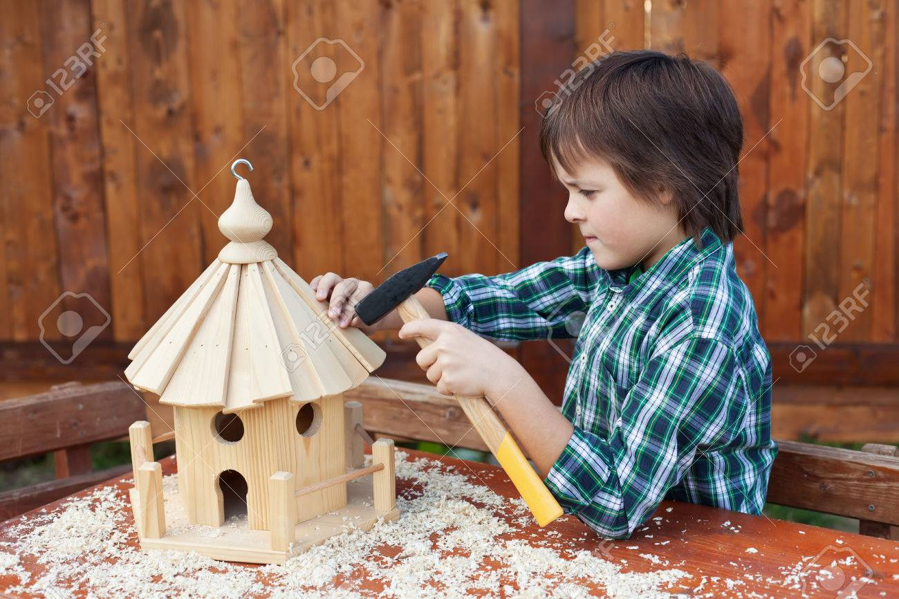 Pleasing Boy Building A Bird House Mounting The Last Roof Piece With Download Free Architecture Designs Scobabritishbridgeorg
