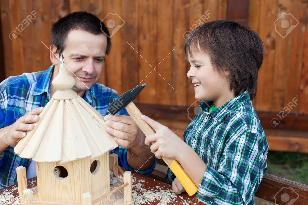 Father and son building a bird house or feeder for the winter time - 24081259